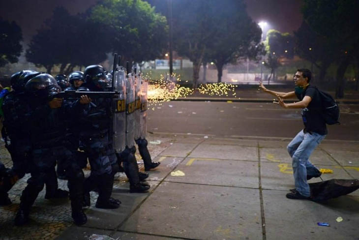 A Brazilian protester stands before gunfire during protests against corruption and police brutality.