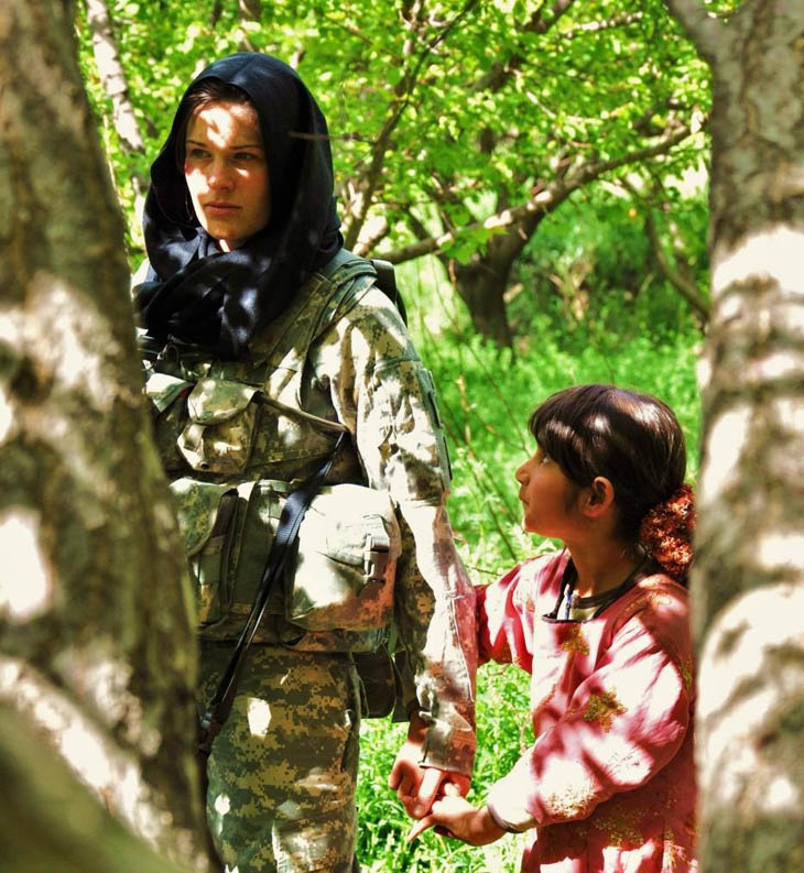 A curious Afghan girl holds the hand of an American soldier.