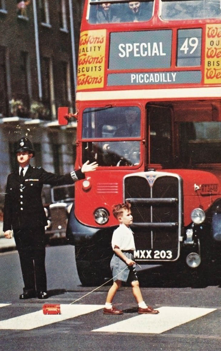 A boy crosses a London street in the 1960s with a toy double decker.