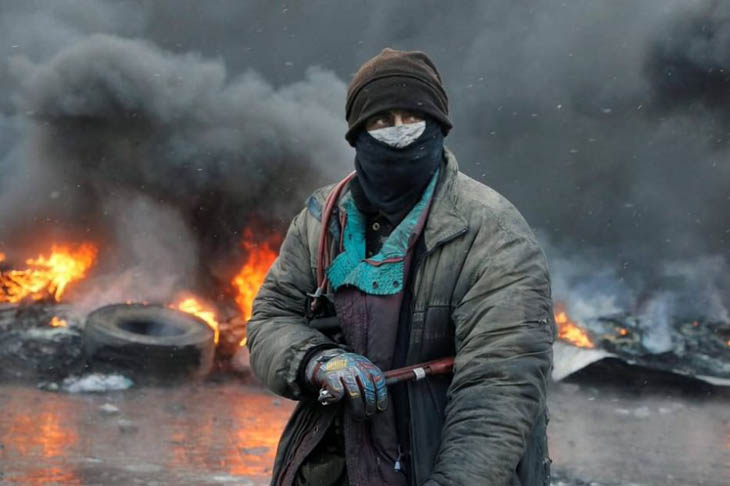 A protester stands at a burning barricade between police and protesters in central Kiev.