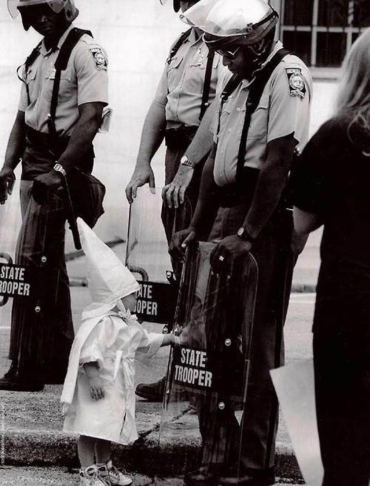 The child of a KKK member touches his reflection