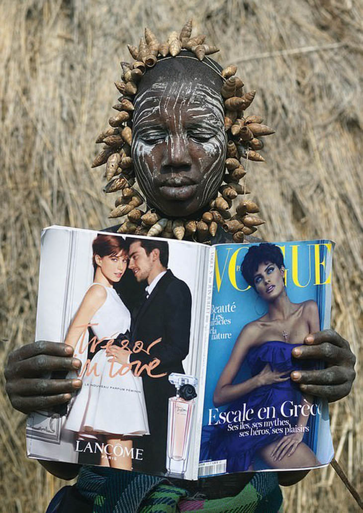 A Mursi tribe woman discovers Vogue magazine, Ethiopia