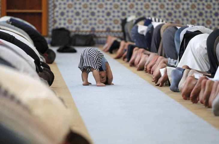 A child with members of the Muslim community attending midday prayers