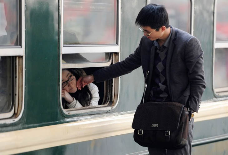 A young girl saying goodbye through a train window at Hefei, Anhui Province.