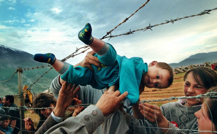 Agim Shala is passed through a barbed wire fence to his grandparents at a camp for refugees of the Kosovo War