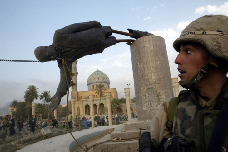 A month and a half after the invasion began, U.S. Marine Kirk Dalrymple watches as a statue of Iraq's President Saddam Hussein falls in central Baghdad. [2003]