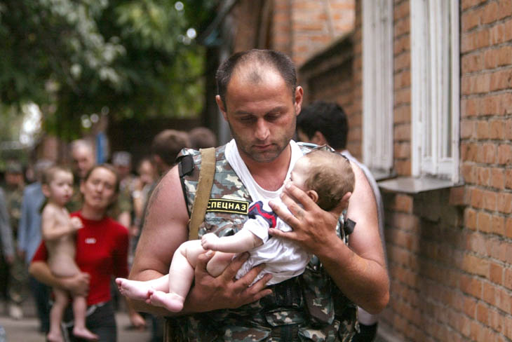 A Russian police officer carries a released baby from the school