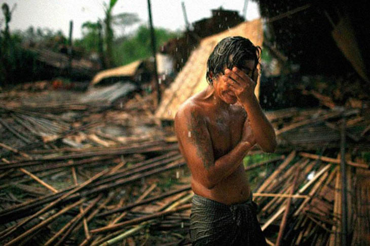 Hhaing The Yu, 29, holds his face in his hand as rain falls on the decimated remains of his home