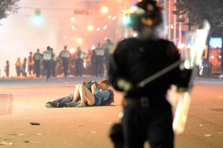 21st century photos - A couple kisses on the pavement during the Vancouver Riot [2011]
