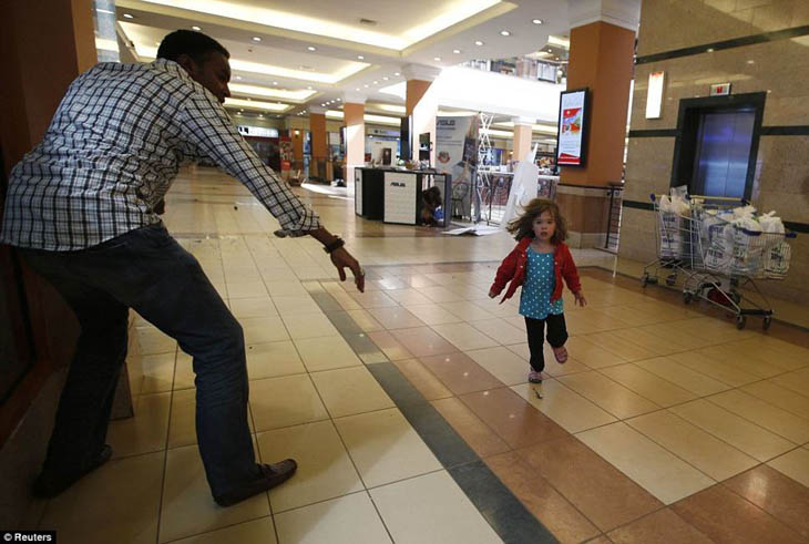 A child runs to safety as armed police hunt gunmen who went on a shooting spree at Westgate shopping centre in Nairobi.