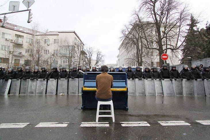 21st century photos - Markiyan Matsekh plays piano for police during the Ukranian revoloution. [2014]