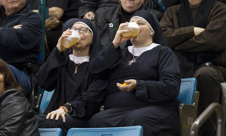 Two women wearing nun outfits drink beer while watching the 2014 Tim Hortons Brier curling championships in Kamloops, British Columbia.