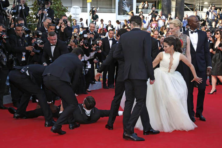 A man is arrested by security as he tries to slip under the dress of actress America Ferrera in Cannes.