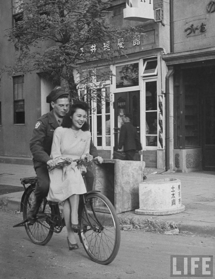 Wartime photos:US Soldier Giving Japanese Girl A Bicycle Ride, With Handlebar Riding Forbidden, 1946, Japan