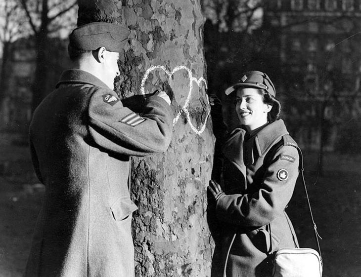 Young Couple Chalking Hearts Onto A Tree, Valentine's Day, 1944